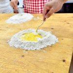 木の板の上に粉と卵を広げて練るパスタの作り方
